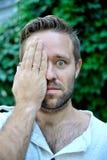 年轻人用手报道一半他的面孔 免版税库存照片