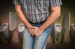 人用拿着他的裤裆的手,他要撒尿 库存图片