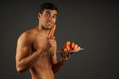 年轻人用红萝卜 免版税库存图片