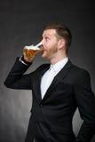 年轻人用胡子饮用的啤酒 免版税库存图片