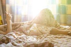 人用途智能手机早晨,当在家在床上在毯子v下时 免版税库存图片