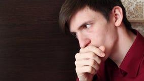 年轻人用他的手,在他的嘴唇的食指盖了他的嘴,仔细地看 影视素材