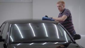 人由布料在汽车盥洗室,摩擦屋顶清洗汽车,去掉土从表面 股票视频