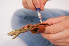 人由有扣的手皮带做 手工制造爱好 休息由制造他的设计师传送带的年轻人 有螺丝的人 库存照片
