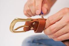 人由有扣的手皮带做 手工制造爱好 休息由制造他的设计师传送带的年轻人 有螺丝的人 图库摄影