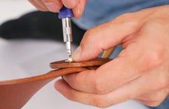 人由有扣的手皮带做 手工制造爱好 休息由制造他的设计师传送带的年轻人 有螺丝的人 库存图片