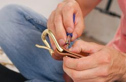 人由有扣的手皮带做 手工制造爱好 休息由制造他的设计师传送带的年轻人 有螺丝的人 免版税库存图片