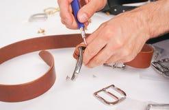 人由有扣的手皮带做 手工制造爱好 休息由制造他的设计师传送带的年轻人 有螺丝的人 免版税图库摄影