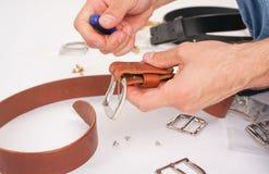 人由有扣的手皮带做 手工制造爱好 休息由制造他的设计师传送带的年轻人 有螺丝的人 免版税库存照片