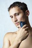 人由电动剃须刀刮了他的下巴 免版税库存图片
