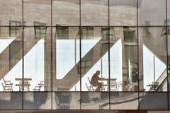 人由看他的在玻璃段落的桌坐手机 免版税图库摄影
