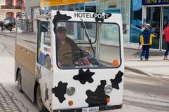 人由策马特驾驶电送货车,瑞士街道  免版税库存照片