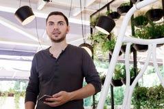 人男孩年轻咖啡馆温室花设计内部愉快的许多罐另外植物画象绿色卖花人工作庭院离开 免版税库存照片
