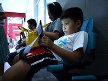 年轻人男孩打在片剂的一个电子游戏,当在算术讲解类的一个等候室时 库存图片