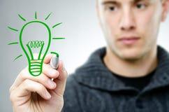 人画一个绿色电灯泡 免版税图库摄影