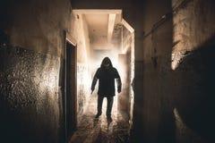 人疯子或凶手或者恐怖凶手剪影有刀子的在手中在黑暗的蠕动和鬼的走廊 犯罪强盗 库存图片