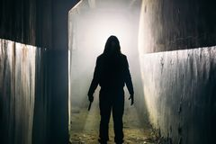 人疯子或凶手或者恐怖凶手剪影有刀子的在手中在黑暗的蠕动和鬼的走廊 免版税库存照片