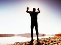 人疯狂跳跃在海滩 在海滩的运动员飞行在天际上的日出期间 免版税库存图片