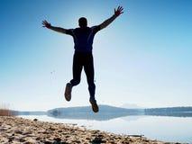 人疯狂跳跃在海滩 在海滩的运动员飞行在天际上的日出期间 免版税库存照片