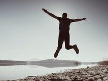 人疯狂跳跃在海滩 在海滩的运动员飞行在天际上的日出期间 图库摄影