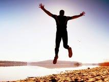 人疯狂跳跃在海滩 在海滩的运动员飞行在天际上的日出期间 免版税图库摄影