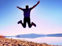 人疯狂跳跃在海滩 在海滩的运动员飞行在天际上的日出期间 库存图片