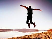 人疯狂跳跃在海滩 在海滩的运动员飞行在天际上的日出期间 库存照片