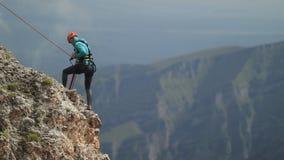 人登山人轻轻地下降对峭壁的边缘 股票录像