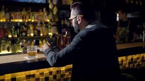 人的一份饮料 人饮用的威士忌酒的播种的特写镜头在酒吧的 影视素材