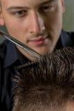 人的与剪刀的头发切口在美容院 免版税库存图片
