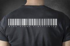 人的交易的tittle和条形码在黑T恤杉 backarrow 库存照片