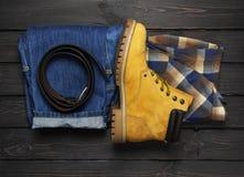 人的便衣、黄色工作靴子从自然nubuck皮革,蓝色牛仔裤、方格的衬衣和棕色传送带在黑暗木 免版税库存图片