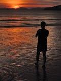 人的剪影观察在海的镇静正面日落在泰国, Ao Nang海滩,甲米府 免版税图库摄影