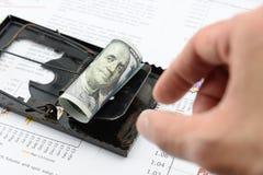 人的右手准备采摘滚动美国100美金纸卷在一个黑鼠陷井 免版税图库摄影