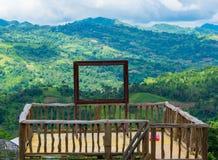 人的在一个平台的大小木相框有一个绿色森林和山的背景在一晴朗的清楚的天空蔚蓝 库存照片