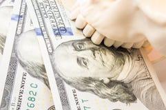 人的头骨举行不顾100个美国美金的上部和下颌 形象化小室工作的价值或价格的概念  免版税库存照片