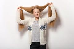 人的姿势表示和情感 显示舒适的运动衫的年轻可爱的红头发人妇女拿着她华美的特长natur 免版税库存图片