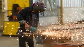 人的工作钢研磨机在工厂 免版税库存图片