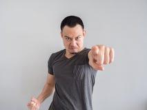 人的恼怒和疯狂的面孔黑T恤杉的 库存照片