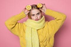 人的情感 黄色毛线衣和围巾陈列滑稽的面孔的白肤金发的美丽的欧洲女孩,拿着两被切的柑橘 免版税图库摄影