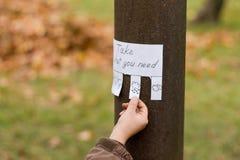 人的手为与天气象的手写的广告保持 免版税图库摄影