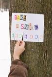 人的手为与词组的纸广告保持:采取微笑,并且与准备好微笑的标志是草率了凑成 库存图片
