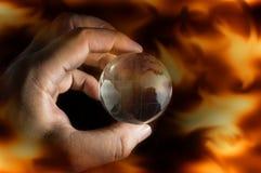 人的手举行地球,火火焰屏幕 库存照片