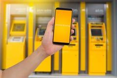 人的手举行巧妙的电话,片剂,有真正app互联网银行业务的手机在模糊的现钞机背景 库存照片