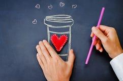 人的手举行杯在一个黑板的咖啡华伦泰的 库存图片
