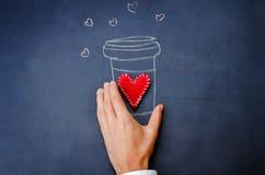 人的手举行杯在一个黑板的咖啡华伦泰的 免版税库存图片