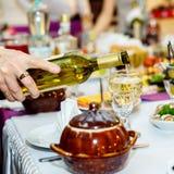 人的手倒白葡萄酒到葡萄酒杯 免版税库存图片