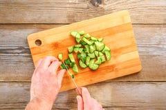 人的手削减了okroshki的光在一张老木桌上的一个切板 免版税图库摄影