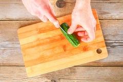 人的手削减了okroshki的光在一张老木桌上的一个切板 免版税库存图片