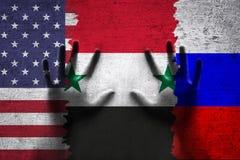 人的手和叙利亚美国和俄罗斯被撕毁的旗子 免版税库存照片